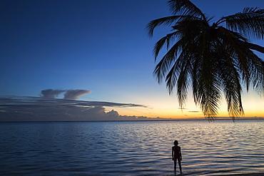 Woman at sunrise at Meeru Island Resort, Meerufenfushi, North-Male-Atoll, Maldives