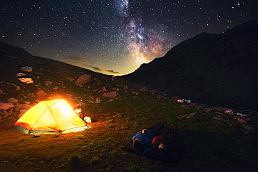 Two hikers watch the starry sky and milky way, camping spot in the Pfunderer Mountains, South Tyrol, Italy