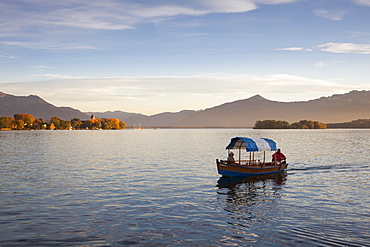 Couple in a boat, view to Fraueninsel, near Gstadt, Chiemsee, Chiemgau region, Bavaria, Germany