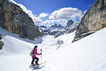 Female back-country skier ascending to Hochebenkofel, Sexten Dolomites, South Tyrol, Italy