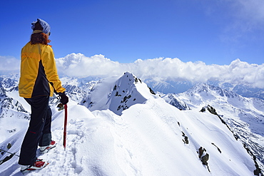 Female back-country skier at summit of Piz Buin and looking at mountain panorama, Silvretta Range, Lower Engadin, Engadin, Grisons, Switzerland