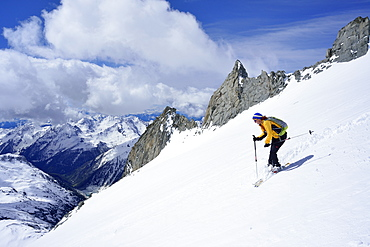 Female back-country skier downhill skiing from Grosser Moeseler, Zillertal Alps, South Tyrol, Italy