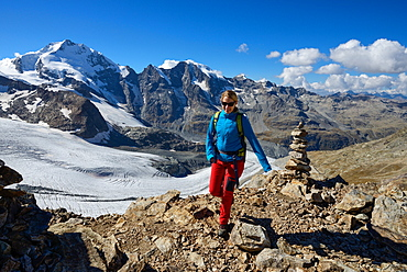 Woman at the summit of Piz Trovat (3146 m) with view to the Bernina-Alps with Bellavista (3922 m), Piz Bernina (4049 m), Piz Morteratsch (3751 m) as well as Pers- and Morteratsch glacier, Engadin, Grisons, Switzerland