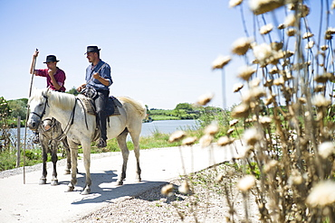 Gardians and their Camargue horse in front of their Manade, near Aigues-Mortes, Camargue, Gard, Languedoc-Roussillon, France