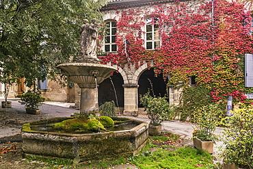 Fountain in Saignon, facade with wild wine in autumn, Provence-Alpes-Cote d'Azur, France