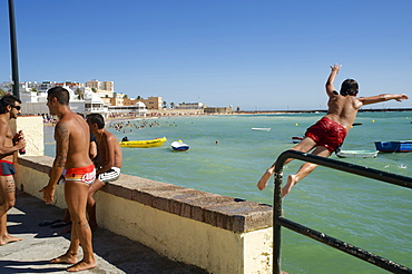 3 men on the beach and one boy jumping from the harbour wall into the sea next to the Castillo de Santa Catalina, Cadiz, Andalusia, Spain, Europe