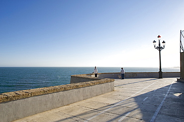 Promenade by the sea with wall and old style electric light, view across the sea with two lonesome people, Cadiz, Andalusia, Spain, Europe