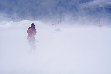 A backcountry skier with a DSLR camera taking a picture in a storm caused by Foehn winds, summit of the Mattjisch Horn, high valley called Fondei, Grison Alps, canton of Grison, Switzerland