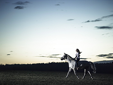 girl riding her horse at dusk, Freising, Bavaria, Germany