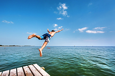 Boy diving from a pier, South beach, Burgtiefe, Fehmarn island, Baltic Coast, Schleswig-Holstein, Germany