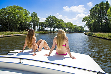 Two Young women wearing a bikini relaxing on the deck of a Le Boat Royal Mystique houseboat on the Plassendale - Niuewpoort canal, near Bruges, Flemish Region, Belgium