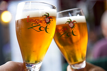 Toasting with two glasses of Brugse Zot beer in a restaurant in the Old Town, Bruges Brugge, Flemish Region, Belgium
