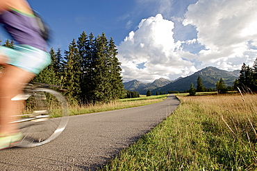 Young woman riding her bike near mountains on a sunny day, Tannheimer Tal, Tyrol, Austria