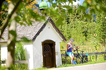 Young female cyclist having a break and reading a map, Tannheimer Tal, Tyrol, Austria