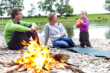 Family sitting around the campfire, Camping along the river Elbe, Family bicycle tour along the river Elbe, adventure, from Torgau to Riesa, Saxony, Germany, Europe