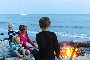 Familiy with children sitting around the campfire, adventure, sailing boat, dream beach between Strandmarken und Dueodde, sandy beach, summer, Baltic sea, Bornholm, Strandmarken, Denmark, Europe, MR