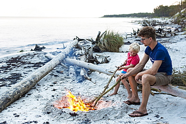 Five year old boy sitting with his father around a campfire, adventure, dream beach between Strandmarken und Dueodde, sandy beach, summer, Baltic sea, Bornholm, Strandmarken, Denmark, Europe, MR