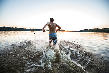 Young man running into the water of a lake, Freilassing, Bavaria, Germany