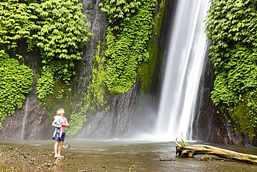 Father and son looking at Air Terjun Munduk waterfall, Munduk, Bali, Indonesia