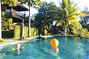 Boy bathing in a hotel swimming pool, Sidemen, Bali, Indonesia