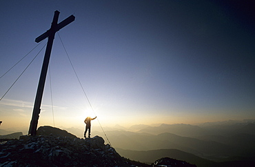 Hicker in front of summit cross of the Benediktenwand, Bavarian foothills of the Alps, Upper Bavaria, Bavaria, Germany