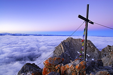 Summit cross with prayer flags on mountain Ellmauer Halt, Kaiser range, Tyrol, Austria