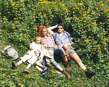 Family lying on grass, Eng, Kleiner Ahornboden, Tyrol, Austria