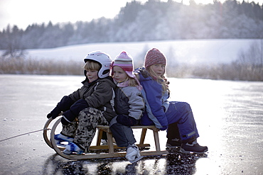 Children sitting on sledge on frozen lake Buchsee, Munsing, Bavaria, Germany