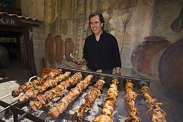 Agis Jacovides, managing director, at a charcoal grill full of quails, The Village Tavern, Pano Platres, South Cyprus, Cyprus