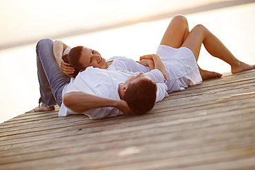 Couple lying on a jetty, Ambach, Lake Starnberg, Bavaria, Germany