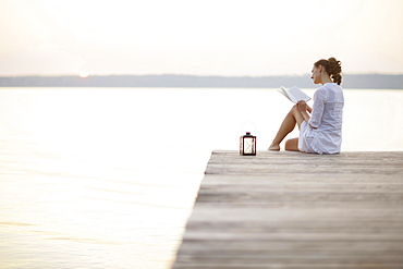 Woman sitting on jetty at lake Starnberg while reading a book, Ambach, Bavaria, Germany