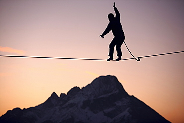Man balancing on a slackline in sunset, Oberstdorf, Bavaria, Germany