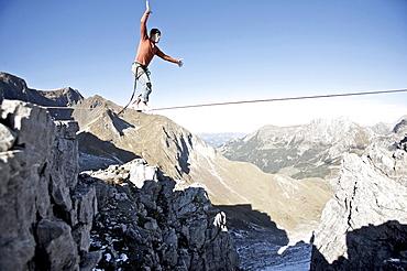 Young man balancing on a slackline, Oberstdorf, Bavaria, Germany