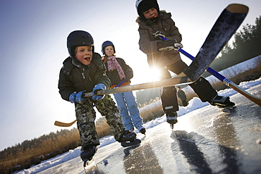 Children playing hockey on lake Buchsee, Munsing, Upper Bavaria, Germany