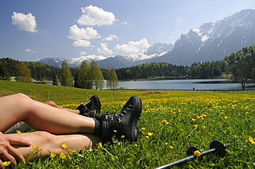 Couple hiking at Lautersee, having a rest, Mittenwald, View towards Karwendel Mountain Range, Upper Bavaria, Bavaria, Germany, Europe