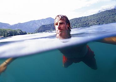 Young man swimming in lake Lago di Levico, Valsugana, Trentino-Alto Adige/Südtirol, Italy