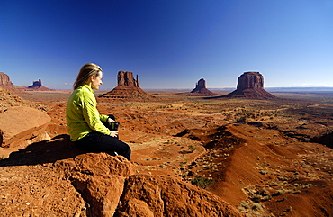 Young woman sitting on a rock looking at the view, Monument Valley, Utah, North America, America