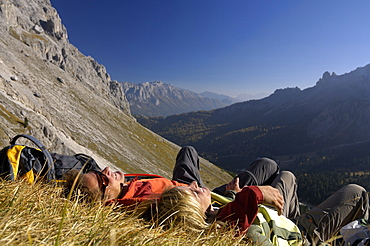 Couple resting on mountain meadow, Val di Fassa, Dolomites, Trentino-Alto Adige/Südtirol, Italy