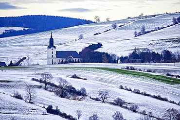 Church between snow-covered fields, Mildenau, Ore Mountains, Saxony, Germany