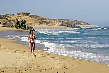 Woman walking along the beach holding her 5 month old baby, Nine Palms, Baja California Sur, Mexico