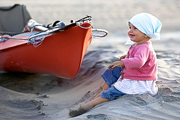 A one year old girl sitting on the beach next to a sea kayak, Punta Conejo, Baja California Sur, Mexico