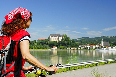 Woman looking over river Danube to Grein, Upper Austria, Austria