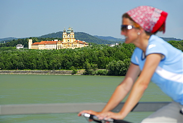 Female cyclist riding along Danube river, Melk abbey in background, Danube Cycle Route Passau to Vienna, Wachau, Lower Austria, Austria
