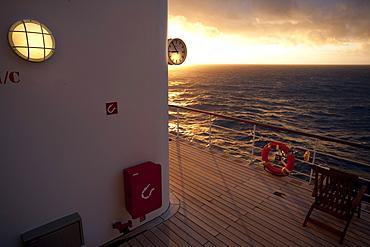 Promenade deck with clock, life buoy and deck chair, sunset, Cruise liner Queen Mary 2, Transatlantic, Atlantic ocean