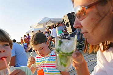 Mother with children in the Pirata Bus beach bar, Formentera, Balearic Islands, Spain