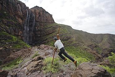 Man jumping with canarian crook in front of the waterfall Cascada el Escobar, El Risco valley, Parque Natural de Tamadaba, Gran Canaria, Canary Islands, Spain, Europe