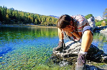 Woman refreshing at a mountain lake, Valley of the seven lakes, Triglav Nationalpark, Julian Alps, Slovenia, Alps.