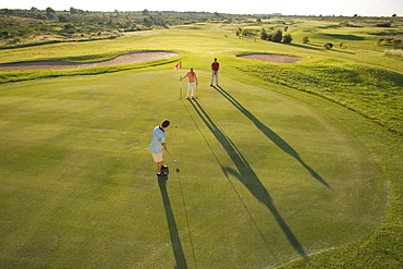 Golfers on golf course, long shadows, Apulia, Italy