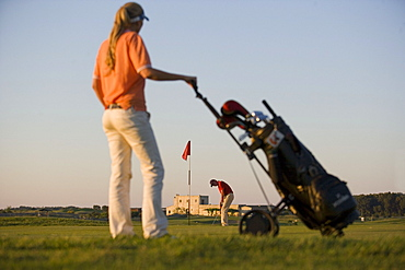 Male golfer preparing to hit ball, woman looking to him, Apulia, Italy