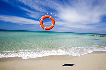 Lifebelt flying over sandy beach, Apulia, Italy